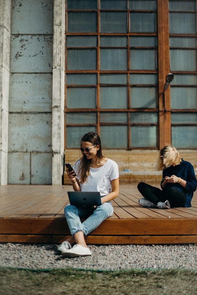 Två tjejer med mobiltelefoner